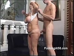 Horny redhead granny gives a young stud a naughty blowjob