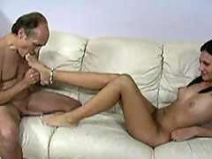 Brunette slut massaging a cock with her feet